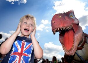 Young boy holding ears next to large dinosaur